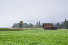 Farmer huts on pasture in fog. Bavarian Alps stock images