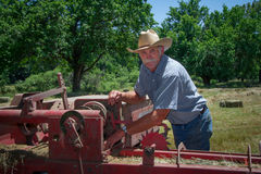 Farmer inspects Equipment Stock Photo