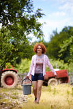 Farmer lady with a bucket in an orchard Stock Photos