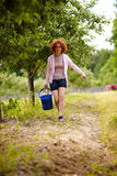 Farmer lady with a bucket in an orchard Stock Photo