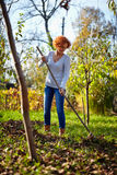 Farmer lady raking, cleaning the garden Stock Photography