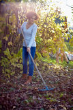 Farmer lady raking, cleaning the garden Royalty Free Stock Image