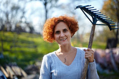 Farmer lady raking, cleaning the garden Stock Photos