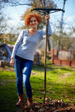 Farmer lady raking, cleaning the garden Royalty Free Stock Photography
