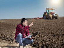 Farmer with laptop on the farmland Stock Images