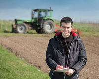Farmer with laptop on the farmland. Young farmer supervising work and writing notes on farmland, tractor harrowing in background Stock Photos