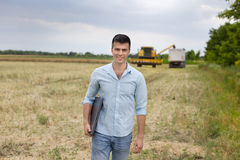 Farmer with laptop in the field. Young attractive farmer carrying laptop in the field during rapeseed harvest stock photo