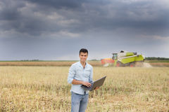Farmer with laptop in the field. Young attractive farmer working on the laptop in the field during rapeseed harvest stock photo