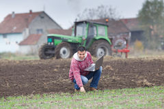 Farmer with laptop. Young farmer with laptop on the field with seedlings in late autumn Royalty Free Stock Image