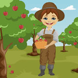 Farmer little boy picking apples holding basket standing in orchard. Smiling Royalty Free Stock Image
