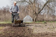 Farmer loosens the soil cultivator Royalty Free Stock Image