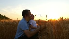A farmer man and his son are considering a wheat crop, being on the field at sunset. Dad and child are happy to look at. The ears of wheat and smile. Slow stock video