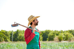 Farmer man with hoe looking at his field Stock Images