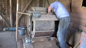 Farmer man spin handle of sifting machine and sift grain in mill Royalty Free Stock Images
