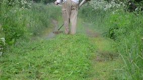 Farmer man trim grass. Worker man farmer cut grass in garden with weed trimmer stock footage