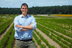 Farmer and meadow. Happy farmer with arms crossed in front of his fields royalty free stock image