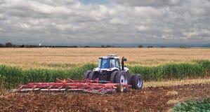 Farmer Mulching corn stubble back into the soil. Stock Photos