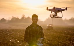 Farmer navigating drone above farmland. Attractive farmer navigating drone above farmland. High technology innovations for increasing productivity in agriculture royalty free stock images