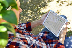 Farmer observing some charts in a tablet Stock Images