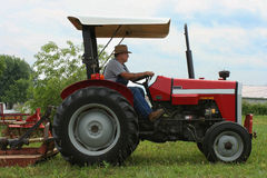 Farmer Operating Tractor. An East Tennessee farmer operates his equipment to till his farm for planting Stock Photo