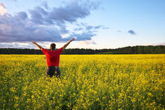 Farmer with outstretched arm at the rape field. Royalty Free Stock Photo