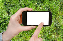 Farmer photographs green grass of lawn. Gardening concept - farmer photographs green grass of lawn on smartphone with cut out screen with blank place for Royalty Free Stock Photography
