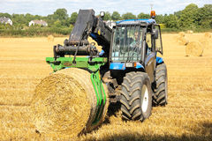 Farmer picking up hay bales. Ireland Royalty Free Stock Images