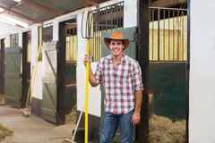 Farmer pitch fork. Happy horse farmer holding pitch fork in stable Royalty Free Stock Photography