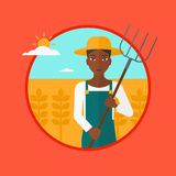 Farmer with pitchfork in wheat field. Royalty Free Stock Images