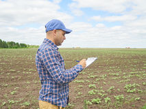 Farmer in plaid shirt controlled his field and writing notes Royalty Free Stock Photo