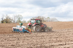 Farmer planting the spring crop with an agricultural planter Royalty Free Stock Photo