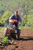 Farmer plowing. Farmer till the ground for setting potatoes Stock Photo
