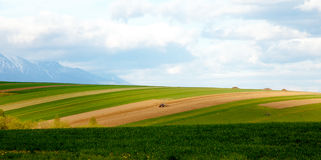Farmer plowing the field. Cultivating tractor in the field. Snow mountain in background. Royalty Free Stock Photos