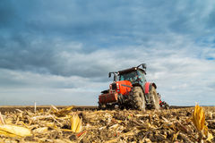 Farmer plowing with red tractor. Royalty Free Stock Image