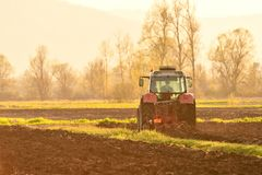 Farmer plowing soil at sunset in spring time Stock Image