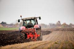 Farmer plowing stubble field stock photo