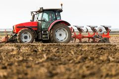 Farmer plowing stubble field stock image