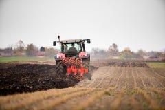 Farmer plowing stubble field stock photography