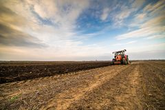 Farmer plowing stubble field stock photos