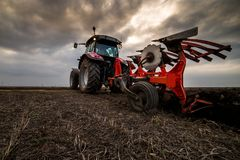 Farmer plowing stubble field royalty free stock images