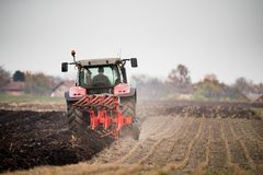 Farmer plowing stubble field royalty free stock image