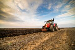 Farmer plowing stubble field royalty free stock photo