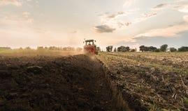 Farmer plowing stubble field Royalty Free Stock Image