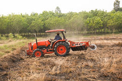 Farmer plowing stubble field with orange tractor stock images