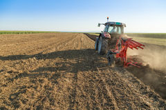 Farmer plowing stubble field with red tractor royalty free stock photography