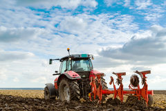 Farmer plowing stubble field with red tractor. stock photography