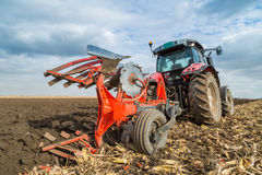 Farmer plowing stubble field with red tractor. Royalty Free Stock Photography