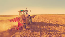 Farmer plowing stubble field with red tractor Stock Photos