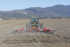 A farmer plows her field. Near a mountainous region Royalty Free Stock Photos