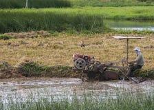 Farmer plows through muddy rice paddy with motorized machine. stock photos